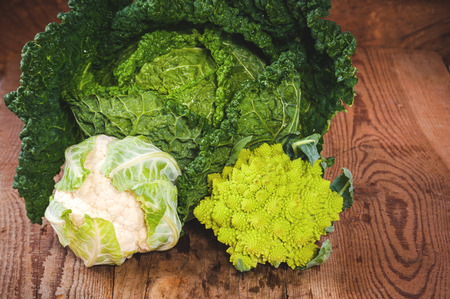 Savoy cabbage with cauliflower and romanesco on a wooden rustic table photo