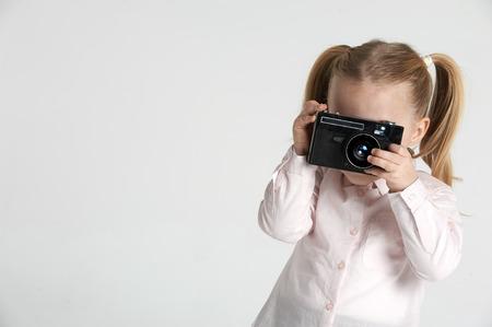 Lachend en met plezier de fotografe een mooie blonde meisje op een witte achtergrond Stockfoto