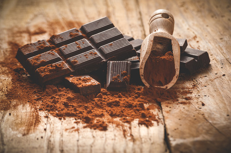 cacao: Noble dark chocolate on a wooden table in vintage style.