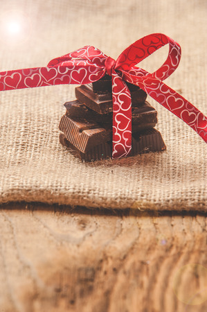 Chocolate with ribbon and heart on St. Valentines day love. photo