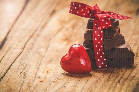 golosinas: Chocolate con la cinta y el coraz�n en el d�a de amor de San Valent�n.
