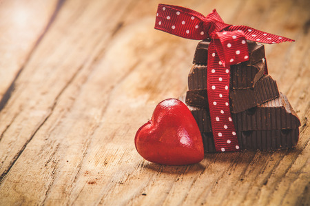romance background: Chocolate with ribbon and heart on St. Valentines day love.
