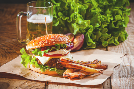 Delicious a burger and fries with a beer in the background onion and lettuce on a wooden rustic table.