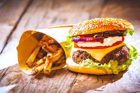 맛있는 햄버거와 칩, 소박한 테이블에 집에서 손으로 만든
