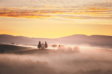 orcia: Sunrise over the chapel Vitaleta, beautiful landscape in the mist of Tuscany, Italy.