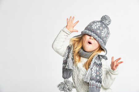 Beautiful blond girl playing in the winter warm hat and scarf on a white background photo