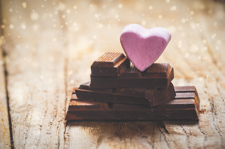 broken love: Pink heart on a black chocolate with rustic wooden background