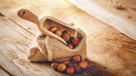 Hazelnuts in a rural bag on a wooden table and a spoon for scooping. photo
