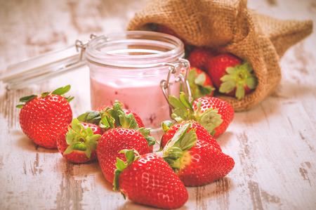 stole: Wiosenne owoce, truskawki w lnianym worku z truskawkowym jogurtem na vintage drewnianym stole.