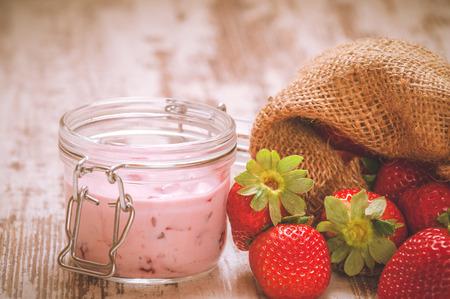Wiosenne owoce, truskawki w lnianym worku z truskawkowym jogurtem na vintage drewnianym stole. photo