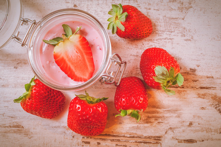 Spring fruits, strawberries with strawberry yogurt on a vintage wooden table. photo