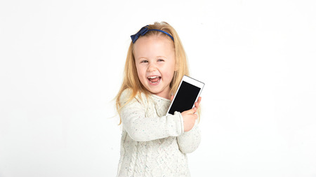 Cute little girl smiling and uses a smartphone, phone. Фото со стока - 35647308