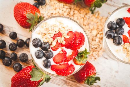 comiendo cereal: Las fresas, ar�ndanos y cereales de desayuno en el yogur en una mesa de madera r�stica