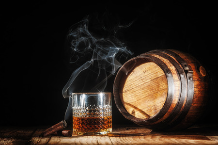 smoking a cigar: Glass of alcohol and smoking noble cigar on a black background