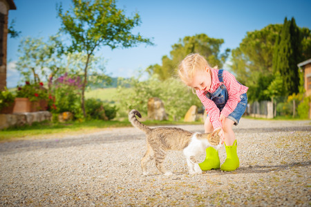 Little Girl and cat playing outdoor in spring beautiful day