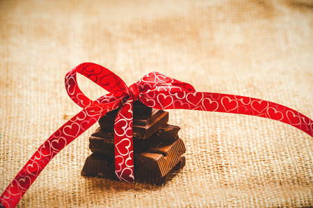Chocolate with ribbon and heart on St. Valentine's day love. Stock Photo