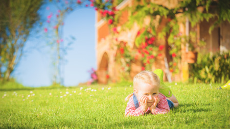 suny: Beautiful smiling little girl playing on the green grass in spring suny day.