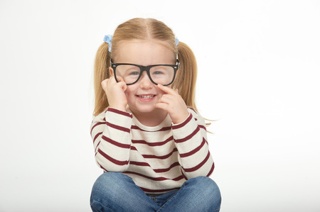Cute little girl with glasses on a white background photo