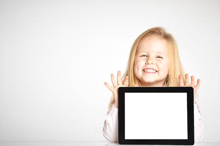 귀여운와 웃는 소녀는 태블릿과 함께 재생