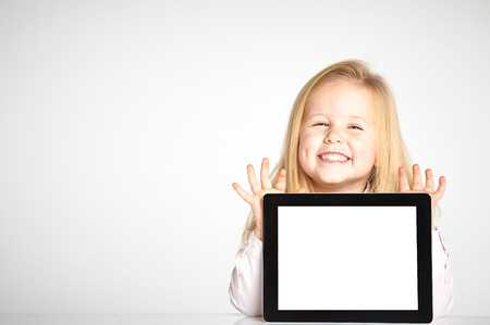 Cute little and smiling girl plays with a tablet