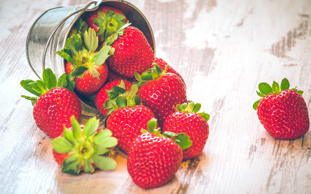 strawberry baskets: Spring fruits, strawberries in an aluminum bucket on a vintage wooden table.
