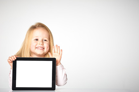 Cute little and smiling girl plays with a tablet Фото со стока - 37137461