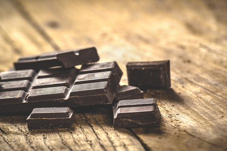 chocolate treats: Noble dark chocolate on a wooden table in vintage style.