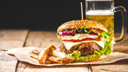 classic burger: Fresh and juicy hamburger on a paper pad with a beer on a wooden table.