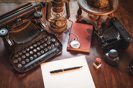Vintage items, camera, pen, globe, clock, typewriter on the old desk photo