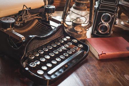 vintage photography stilleven met schrijfmachine, vouwen camera, globe kaart en boek op een houten tafel.
