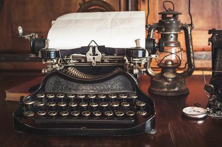 maquina de escribir: la fotograf�a del vintage todav�a la vida con la m�quina de escribir, c�mara plegable, mapa del mundo y libro sobre una mesa de madera. Foto de archivo