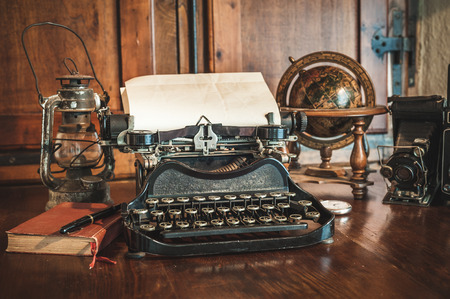 vintage photography still life with typewriter, folding camera, globe map and book on a wood table.
