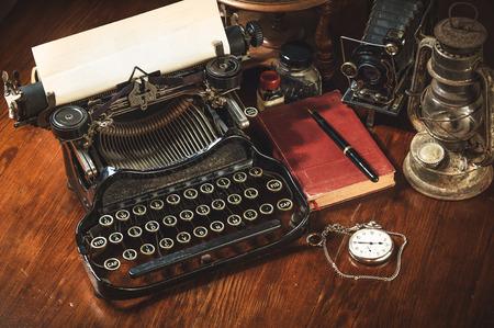 maquina de escribir: Forma tradicional y antiguo de la escritura de mensajes y tomando fotos, m�quina de escribir, c�mara, reloj, pluma, L�mpara de la vendimia en el escritorio Foto de archivo