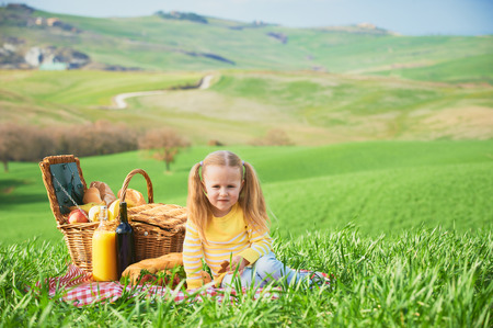 Blonde girl eaten biscuit, fruit on a picnic with landscape of Tuscany background