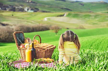 the tuscany: Little girl reversed back doing a picnic in the countryside of Tuscany.