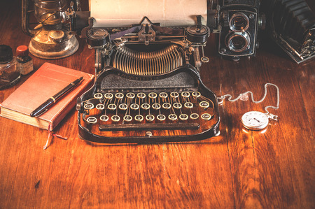 Traditional and old way of writing messages and taking photos, typewriter, camera, watch, pen, Vintage lamp on the desk Фото со стока - 37348986