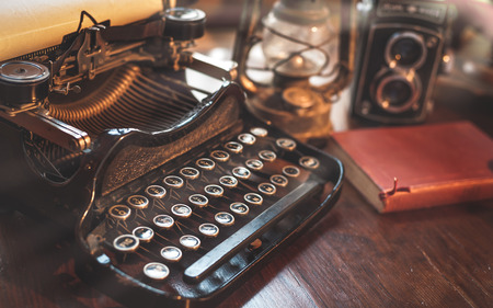 vintage photography still life with typewriter, folding camera, globe map and book on a wood table. Фото со стока - 37348999
