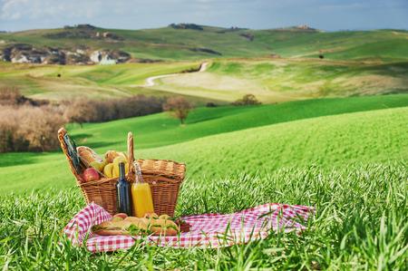 Toscaanse picknick op het groene lentegras met landschap op de achtergrond Stockfoto - 37349000