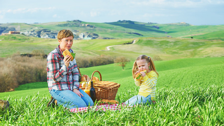 Mother and daughter arranged picnic on the green spring grass in the landscape of Tuscany. photo