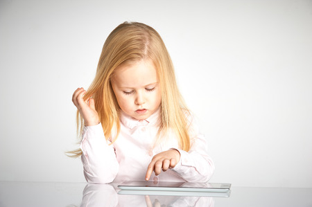 smiling girl: Cute little and smiling girl plays with a tablet
