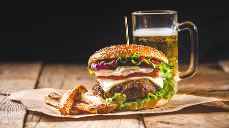 Fresh and juicy hamburger on a paper pad with a beer on a wooden table.