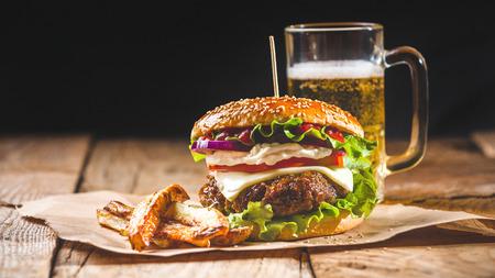 Verse en sappige hamburger op een papieren pad met een biertje op een houten tafel.