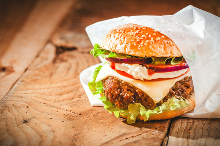 Tasty hamburger with fast food in a white paper on the wooden table.
