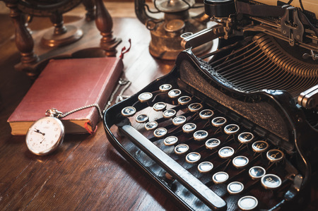 vintage photography still life with typewriter, folding camera, globe map and book on a wood table. photo