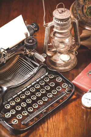 Traditional and old way of writing messages and taking photos, typewriter, camera, watch, pen, Vintage lamp on the desk