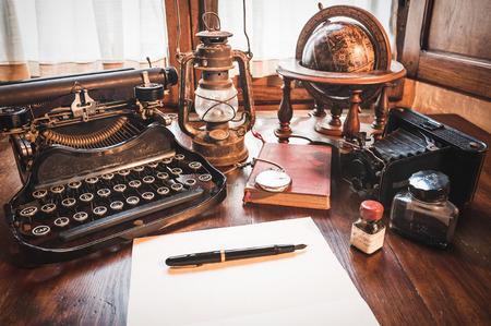 ヴィンテージ商品、カメラ、ペン、グローブ、時計、古い机の上タイプライター