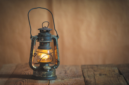 vintage kerosene oil lantern lamp burning with a soft glow light in an antique rustic country barn with aged wood floor