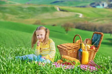 picnic cloth: Beautiful smiling girl on green spring grass in the background landscape of Tuscany. Stock Photo