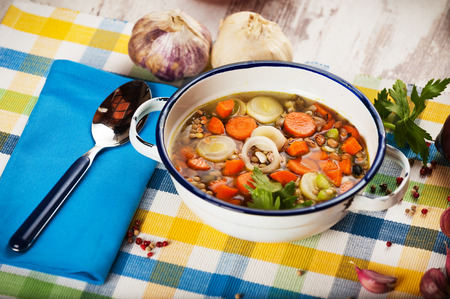 Vegetable soup in a metal bowl on a rural rustic wooden table. photo