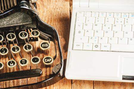 Closeup of a modern laptop computer and an antique typewriter